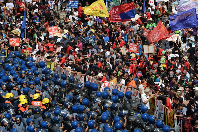 Philippine police (L) block protesters (R) parading down a street trying to voice their opposition to the Asia-Pacific Economic Cooperation (APEC) Summit currently taking place in Manila on November 19, 2015. Police and protesters clashed on November 19 outside the gathering of Asia-Pacific leaders who were meeting for a summit dominated by a US-China tussle for regional influence. AFP PHOTO / Punit PARANJPE